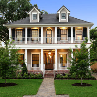 Large traditional beige two-story wood exterior home idea in Houston with a hip roof