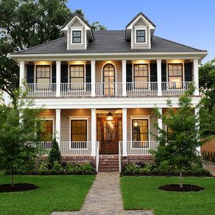 Großes, Zweistöckiges, Beigefarbenes Klassisches Haus mit Holzfassade, Walmdach und Dachgaube in Houston