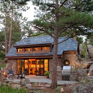 Immagine della facciata di una casa unifamiliare piccola marrone rustica a un piano con rivestimento in pietra, copertura a scandole e tetto a padiglione