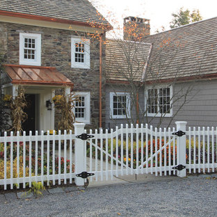 Large and gey rural two floor house exterior in New York with stone cladding.