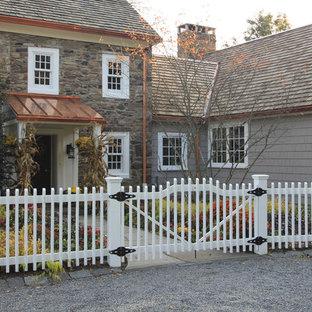 Modelo de fachada gris, de estilo de casa de campo, grande, de dos plantas, con revestimiento de piedra