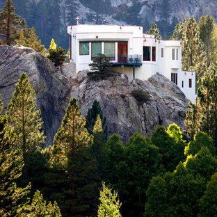 Идея дизайна: белый дом в современном стиле с разными уровнями, плоской крышей и облицовкой из цементной штукатурки