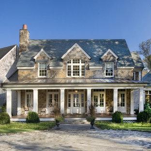 На фото: двухэтажный, большой, коричневый частный загородный дом в классическом стиле с облицовкой из камня, двускатной крышей и крышей из гибкой черепицы с
