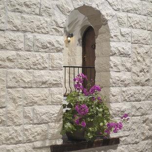Imagen de fachada blanca, mediterránea, pequeña, de dos plantas, con revestimiento de piedra