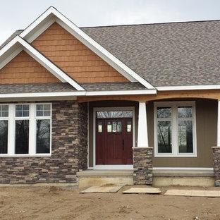 Foto della facciata di una casa unifamiliare marrone american style a un piano di medie dimensioni con rivestimenti misti, tetto a capanna e copertura a scandole