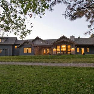 Ejemplo de fachada verde, de estilo de casa de campo, de tamaño medio, de una planta, con revestimientos combinados y tejado a dos aguas