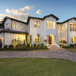 Mid-sized mediterranean white two-story stucco exterior home idea in Tampa with a tile roof