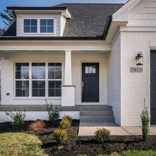 Пример оригинального дизайна: маленький, двухэтажный, белый частный загородный дом в стиле кантри с облицовкой из крашеного кирпича и крышей из гибкой черепицы