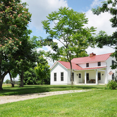 Inspiration for a cottage white two-story exterior home remodel in Louisville with a red roof
