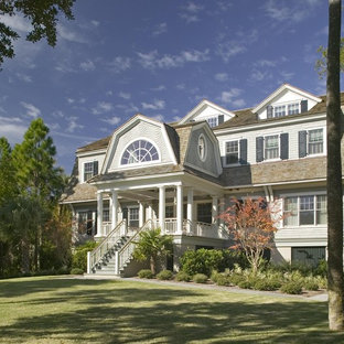 Example of a classic wood exterior home design in Charleston with a gambrel roof