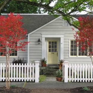 Réalisation d'une façade en bois grise tradition de plain-pied et de taille moyenne avec un toit à deux pans et un toit en shingle.