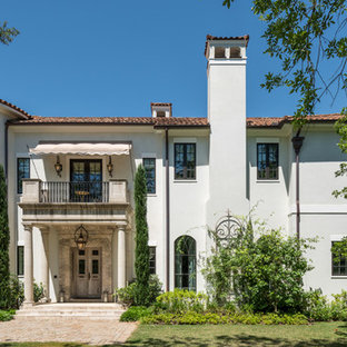 Mediterranean white two-story house exterior idea in Houston with a tile roof