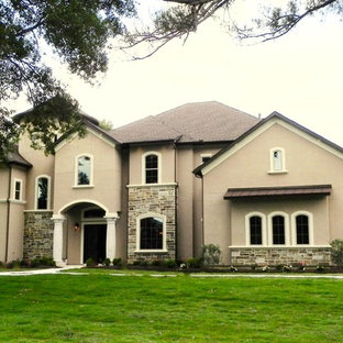 Inspiration for a mid-sized mediterranean beige two-story mixed siding exterior home remodel in Houston with a shingle roof