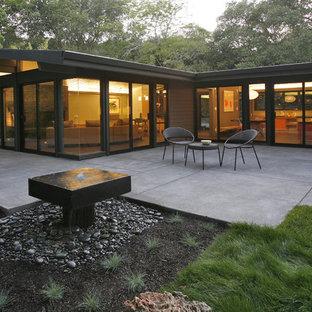 Diseño de fachada de casa vintage, de tamaño medio, de una planta, con revestimiento de vidrio y tejado plano