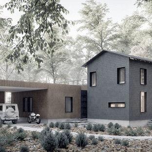 Пример оригинального дизайна: двухэтажный, черный дом среднего размера, из контейнеров в стиле модернизм с комбинированной облицовкой и двускатной крышей
