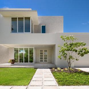 Esempio della facciata di una casa unifamiliare grande bianca moderna a due piani con rivestimento in stucco e tetto piano