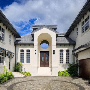 Diseño de fachada de casa blanca, ecléctica, grande, de dos plantas, con revestimiento de estuco, tejado a cuatro aguas y tejado de teja de madera