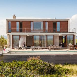Imagen de fachada actual, de dos plantas, con revestimiento de madera y tejado plano