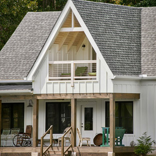 Example of a small country white exterior home design in Other with a shingle roof