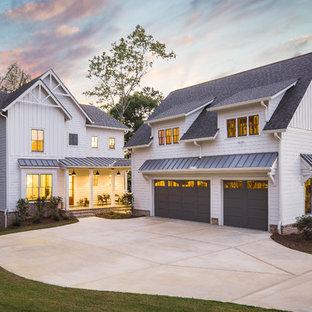 Стильный дизайн: двухэтажный, белый частный загородный дом в стиле кантри с облицовкой из ЦСП, двускатной крышей и крышей из гибкой черепицы - последний тренд