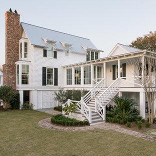 Imagen de fachada de casa blanca, marinera, de tres plantas, con revestimiento de madera, tejado a dos aguas y tejado de metal