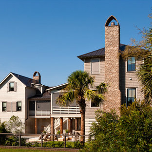 Beach style brown two-story mixed siding exterior home idea in Charleston with a metal roof