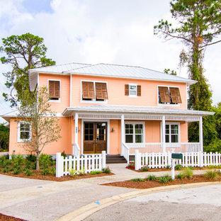 Diseño de fachada de casa naranja, costera, grande, de dos plantas, con revestimiento de vinilo, tejado a la holandesa y tejado de metal