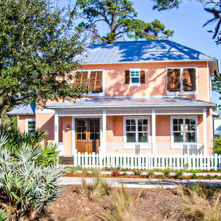 Inspiration for a large beach style two-storey pink exterior in Jacksonville with vinyl siding.