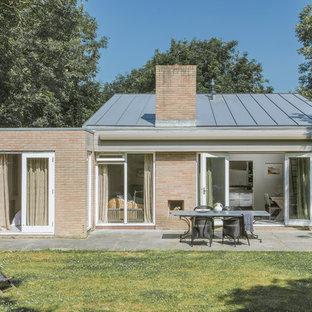 Diseño de fachada beige, marinera, de tamaño medio, de una planta, con revestimiento de ladrillo y tejado de un solo tendido