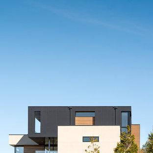 Источник вдохновения для домашнего уюта: большой, трехэтажный, черный дом в современном стиле с облицовкой из цементной штукатурки и плоской крышей