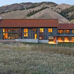 Ispirazione per la facciata di una casa rustica a due piani con rivestimento in legno e copertura in metallo o lamiera