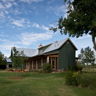 Green farmhouse exterior in Jackson with wood cladding, a pitched roof and a metal roof.