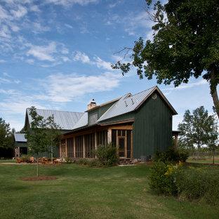 На фото: деревянный, зеленый дом в стиле кантри с двускатной крышей и металлической крышей