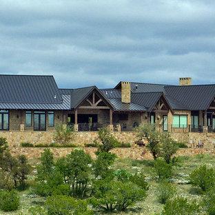 Immagine della facciata di una casa ampia beige rustica a un piano con rivestimento in pietra