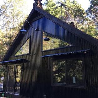 Modelo de fachada negra, bohemia, con revestimiento de metal y tejado a dos aguas