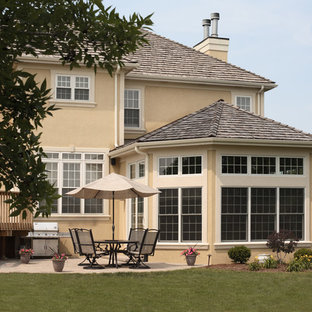 Mid-sized elegant beige one-story stucco gable roof photo in Chicago