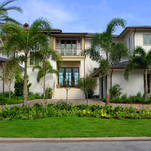 Modelo de fachada de casa blanca, tropical, grande, de dos plantas, con tejado a cuatro aguas, revestimiento de estuco y tejado de teja de madera