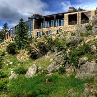 Huge rustic two-story stone exterior home idea in Denver