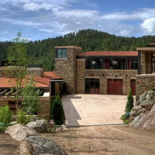 Photo of an expansive rustic two floor house exterior in Denver with stone cladding.