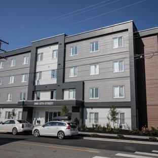 Ispirazione per la facciata di un appartamento grande multicolore contemporaneo a tre piani con rivestimenti misti e tetto piano