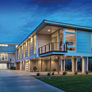 Imagen de fachada de casa beige, costera, grande, a niveles, con tejado a dos aguas