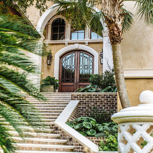 Inspiration for a large mediterranean beige two-story stucco house exterior remodel in Charleston