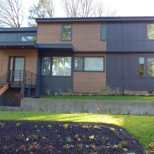 Modelo de fachada de casa negra, contemporánea, grande, de tres plantas, con revestimiento de madera y tejado plano