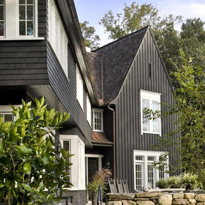 Large traditional black two-story wood, board and batten and shingle gable roof idea in New York