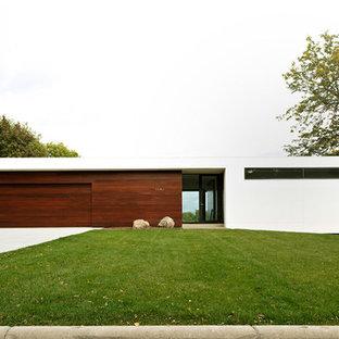 Imagen de fachada blanca, minimalista, de tamaño medio, de una planta, con revestimientos combinados y tejado plano