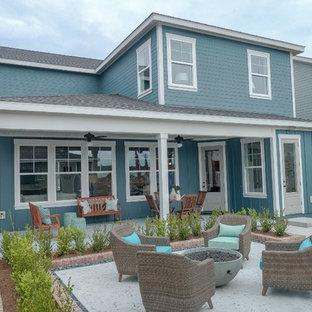 Modelo de fachada de casa azul, costera, de tamaño medio, de dos plantas, con revestimiento de aglomerado de cemento, tejado de un solo tendido y tejado de teja de madera