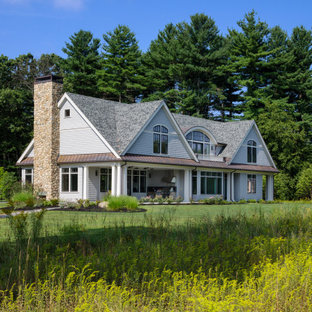 Inspiration for a large cottage gray two-story exterior home remodel in Boston with a mixed material roof