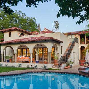 Идея дизайна: двухэтажный, бежевый частный загородный дом с вальмовой крышей и черепичной крышей