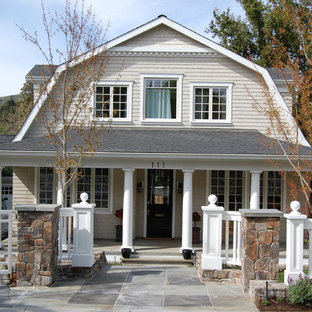 Inspiration for a mid-sized country beige two-story wood house exterior remodel in San Francisco with a gambrel roof and a shingle roof