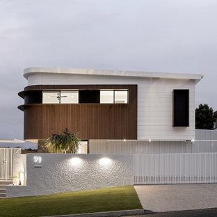 Inspiration för ett stort 60 tals vitt hus, med två våningar, platt tak och tak i metall